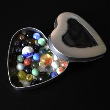 Üveggolyók szív alakú lemezdobozban